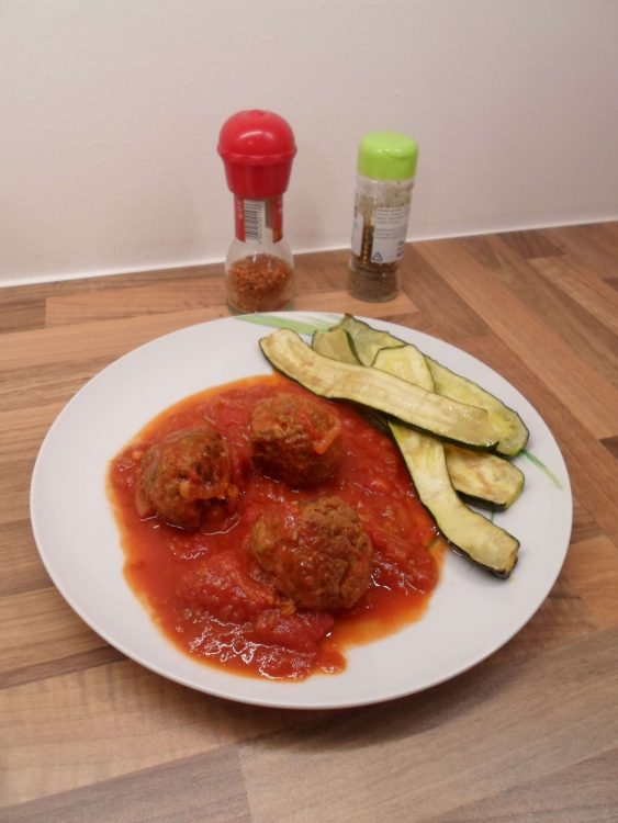 Fleischbällchen mit Tomatensauce und Gewürzen im Hintergrund