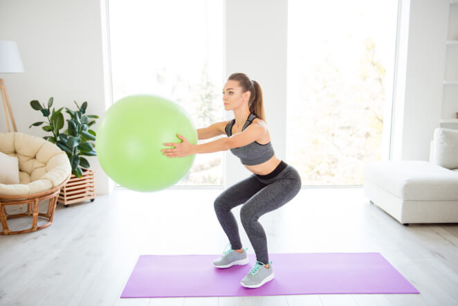 Frau macht Pezziball Übungen im Gymnastikball Training